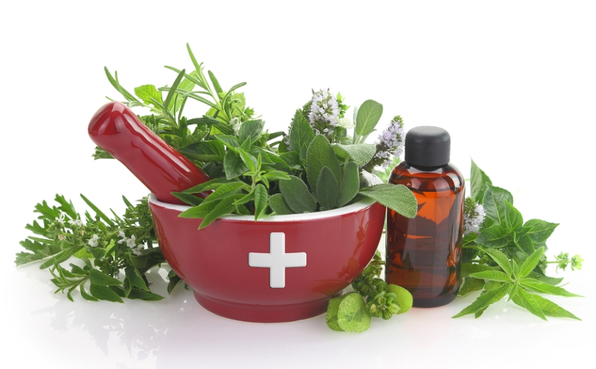 Mortar with medicine cross, fresh herbs and essential oil bottle